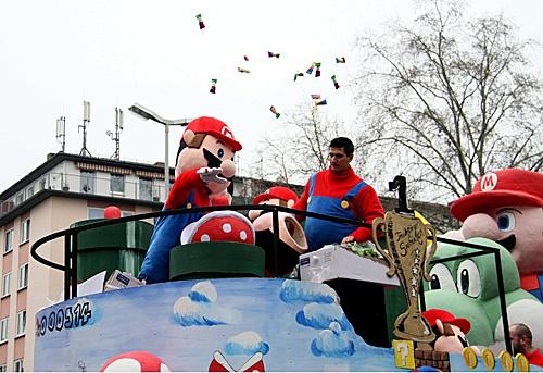 """在德国美因茨""""玫瑰星期一""""大游行上,打扮成""""超级玛丽""""的演员从彩车上向人群抛撒糖果。(新华社)"""